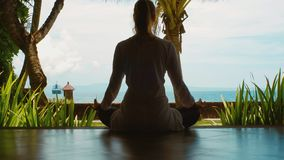 Silhouette of woman is practicing yoga relaxing in lotus position on the ocean beach, beautiful view, nature sounds, close up. Silhouette of woman is relaxing by stock footage