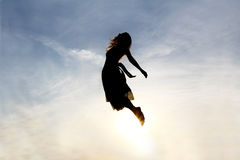 Silhouette of Woman Rising into Heaven. Silhouette of a young woman being raised into the cloudy sky background, as if being sent to Heaven stock image