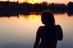 Silhouette of a woman in the river at sunset. Stock Photo