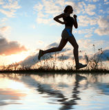 Silhouette woman run under blue sky with clouds. And sun Royalty Free Stock Photos