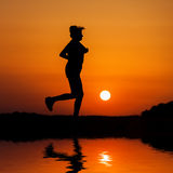 Silhouette woman running against orange sunset Stock Photography