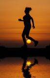 Silhouette woman running against orange sunset Stock Images