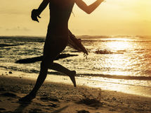 Silhouette of woman running along shore of ocean Royalty Free Stock Photography