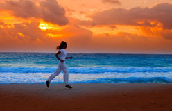 Silhouette of woman, running on sunset along ocean. Coast . Landscape Stock Photography