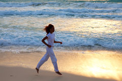 Silhouette of woman, running on sunset along ocean coast.Landscape Stock Images