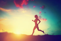 Silhouette of woman running at sunset Stock Photography