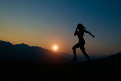 Silhouette of woman running at sunset Stock Photo