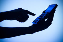 Silhouette of woman's hands with calculator stock images