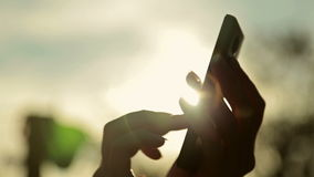Silhouette of woman`s hands with smart phone at sunset. Silhouette of woman hands with smart phone. Typing and touching. Close up shot of mobile cell phone stock video