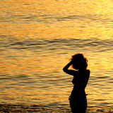 Silhouette of woman at sea. A silhouette of a woman in the water at sunset royalty free stock photo