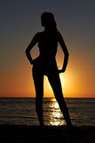 Silhouette of woman on sea coast at sunrise Royalty Free Stock Image