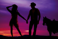 Silhouette woman in sheer dress with cowboy and horse Stock Photo