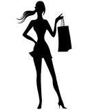 Silhouette of woman with shopping bags in hand Stock Photography