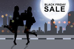 Silhouette woman shopping with paperbag on Black Friday. In the city background Royalty Free Stock Photography