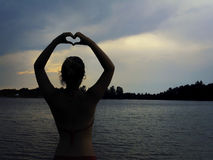 Silhouette of a woman showing heart sign in front of a lake in summer Royalty Free Stock Photography