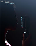 Silhouette of woman singing. Royalty Free Stock Image