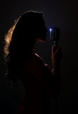 Silhouette of woman singing. Silhouette of woman singing into vintage microphone stock photo