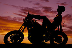 Silhouette of woman sit back on motorcycle hat on Royalty Free Stock Photos
