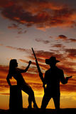 Silhouette woman sit hand up. A silhouette of a women and cowboy, he is holding on to guns Royalty Free Stock Image