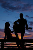 Silhouette woman sit by man with guitar Royalty Free Stock Photos