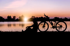 Silhouette woman sit near bicycle on sunset. Stock Photo