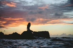 Silhouette of Woman Siting on Rock during Sunset Stock Photography