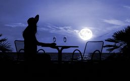 Silhouette of the woman sits at a table Stock Images