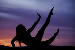 Silhouette of a woman sitting back hand up toes pointed Stock Photo