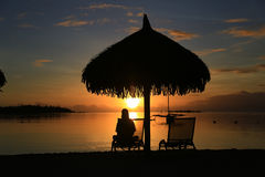 Silhouette of woman sitting on deck chair. Under umbrella, on the beach. Beautiful sunset in the ocean Stock Photo