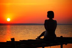 Silhouette of Woman Sitting on Dock during Sunset Stock Image
