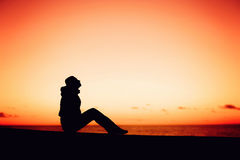 Silhouette of a woman sitting on the edge over Stock Photos