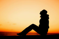 Silhouette of a woman sitting on the edge over Royalty Free Stock Image