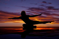 Silhouette of woman sitting on one leg both arms and one leg out Stock Image
