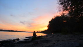 Silhouette of a woman sitting on the river bank stock footage