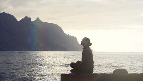 Silhouette of a woman sitting on rocks and observing ocean waves at sunset in Tenerife, Canary Islands. Silhouette of a woman at sunset observing waves stock footage