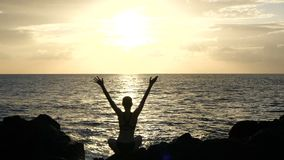 Silhouette of a woman sitting on rocks at sunset observing waves and raising arms in the air. Cinematic slow motion stock video footage