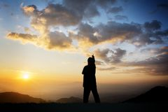 Worship concept. Silhouette of woman sitting at sunset Worship concept Royalty Free Stock Images