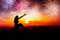 Silhouette of woman sitting and watching the fireworks Stock Images