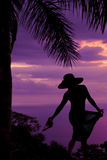Silhouette of a woman  in a skirt and hat hold sandles back Royalty Free Stock Images