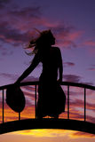 Silhouette of a woman in a skirt hold hat down hair blowing Stock Image