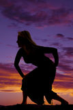 Silhouette of a woman in a skirt posing to the side. A silhouette of a woman crouching down in her sarong as she walks Stock Photo