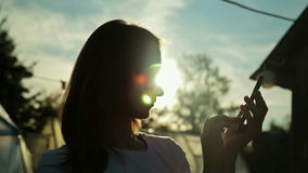 Silhouette of woman with smart phone at sunset. Silhouette of woman with smart phone. Typing and touching. Outdoors in the garden, in nature. Sunset light, sun stock video footage