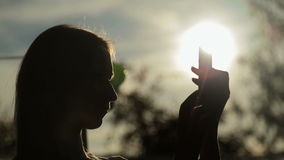 Silhouette of woman with smart phone at sunset stock video footage