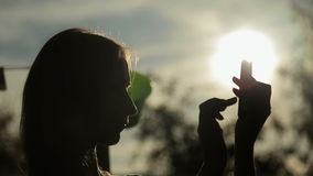 Silhouette of woman with smart phone at sunset. Silhouette of woman with smart phone. Typing and touching. Outdoors in the garden, in nature. Sunset light, sun stock footage
