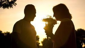 Silhouette of woman smelling flowers presented by man, celebrating anniversary royalty free stock image