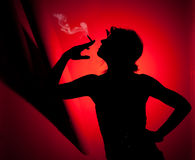 Silhouette of woman smoking. Profile of woman pulling smoke on red background Royalty Free Stock Photos