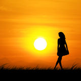 Silhouette of a woman standing in the beautiful sunset. Stock Image
