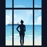 Silhouette of woman standing looking to sea view with boat from her apartment big window Stock Photo
