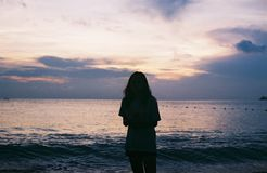 Silhouette of Woman Standing Near Large Body of Water stock photography