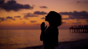 Silhouette of woman is standing on a sea shore in twilight on a background of sunset sky, looking to sea, folding hands. In prayer and rising hands, medium shot stock video